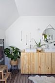 Eckige Aufsatzbecken auf einem Sideboard aus Holz im Bad