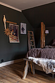 Festive decorations in rustic bedroom with sloping ceiling and dark walls