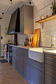 Modern country-house kitchen with blue-grey cupboards and white-tiled wall