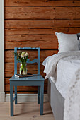 Blue chair used as bedside table next to bed against wooden bedroom wall