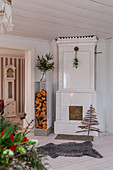 White tiled stove and stacked firewood in living room
