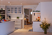 Island counter in festively decorated, white kitchen