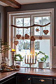 Gingerbread hearts and stars hung from branch in window