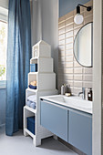 Tower-style shelves in bathroom in blue and white with subway tiles