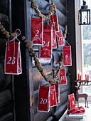 Advent calendar made from red tea packets hung from garland of nuts