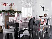Verschiedene Stühle am schwarzen Tisch mit moderner Weihnachtsdeko