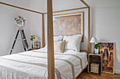 Pale, wooden four-poster bed, studio lamp and wooden crate used as bedside table