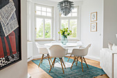 Tulip Table and classic shell chairs in white window bay of period apartment