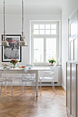 White dining table, Ghost Chairs and silver, industrial-style pendant lamps