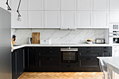 White wall units and black base units in modern kitchen of period apartment