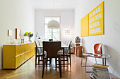 Yellow sideboard in dining room with 70s lamp over table