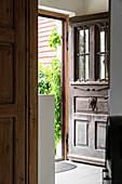Open wooden front door with classic metal doorknocker