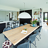 Oak dining table in open-plan interior with black-and-white kitchen in background