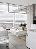 Modern living room decorated entirely in white with sea view through glass wall