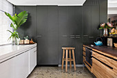 Grey fitted cupboards in kitchen with white and wooden counters