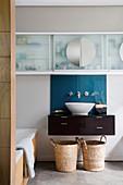 Zwei Körbe unterm Waschbecken mit blauem Spritzschutz