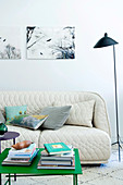 White quilted sofa in front of a modern grass green side table