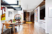 Abstract mural in an open living room with dining table, breakfast bar and spiral staircase