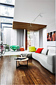 Light gray sofa with chaise longue under gallery in designer apartment