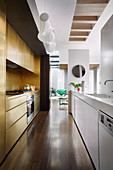 Elongated kitchen with white and gold-colored kitchen units