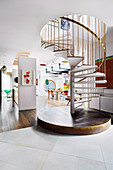 Spiral staircase with a brass-colored railing in the open living room of a designer apartment