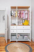White open wardrobe with baby clothes in children's room