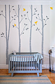 Blue crib in baby room with cheerful wall painting