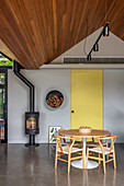 Living room under a pointed wooden roof with a round dining table and cast iron wood stove