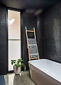 Modern freestanding bathtub in bathroom with black walls and frosted glass windows