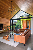 Brown leather corner couch in living room with wooden walls and wooden pointed roof