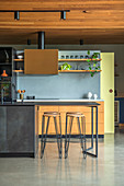 Open kitchen area with light blue kitchen back wall and anthracite-colored breakfast bar