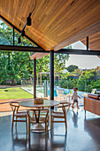 Dining table in open living room under a wooden pointed roof with wide window fronts to the garden