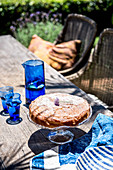 Cakes on a cake stand next to a blue carafe with glasses on a patio table