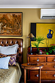 Hunting paintings over a leather bed next to a chest of drawers and wooden side tables