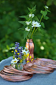 Roll of copper wire and posies of wild summer flowers on table outside