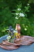 Kupferdrahtrollen und sommerliche Wiesenblumensträußchen auf Tisch im Freien