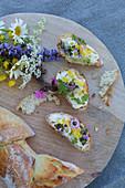 Weißbrot mit Blütenbutter und dekoriert mit sommerlichen Wiesenblumen