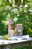 Wildflowers in copper-coloured containers and candles decorated with copper wire