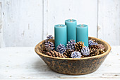 Elegant Christmas arrangement of blue pillar candles and pine cones dipped in coloured wax in bowl