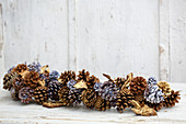 Winter arrangement of leaves and pine cones dipped in coloured wax or sprayed gold