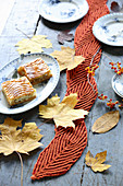 Rusty-red leaf-shaped hand-knitted coasters for decorating autumnal table