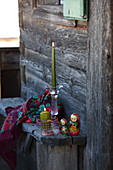 Hand-painted glass candlestick and traditional Russian dolls on wooden bench
