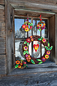 Handmade willow wreaths with felt leaves and felt flowers hung in window