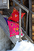 Colourful cushions decorated with ethnic felt flowers and felt hearts