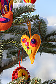 Snow-covered fir tree decorated with handmade felt pendants