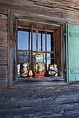 Traditional Russian dolls on windowsill of wooden cabin