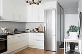 Moderne weiße Küche mit Edelstahlkühlschrank