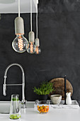 Light bulb pendant lamps above kitchen worksurface against charcoal-grey wall