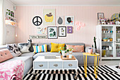 Grey corner sofa with scatter cushions in living room with pink wooden wall