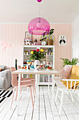 Pink pendant lamp providing a splash of colour above white dining table